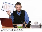 Купить «Office worker shows crossed out schedule sitting in the workplace», фото № 33902265, снято 14 мая 2020 г. (c) Иванов Алексей / Фотобанк Лори