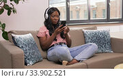 woman with smartphone listening to music at home. Стоковое видео, видеограф Syda Productions / Фотобанк Лори