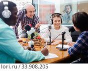 Купить «Multinational group of cheerful young adults emotionally discussing in radio studio», фото № 33908205, снято 16 марта 2019 г. (c) Яков Филимонов / Фотобанк Лори