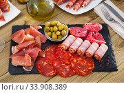 Slices of gammon, chorizo, salami, bacon on slate board. Стоковое фото, фотограф Яков Филимонов / Фотобанк Лори