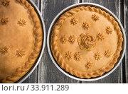 Купить «Two sweet potato pies with edible decorations on top standing on the wooden table», фото № 33911289, снято 12 мая 2020 г. (c) Константин Шишкин / Фотобанк Лори