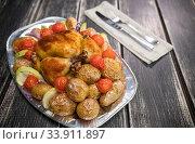 Купить «Chicken baked with potato and green vegetables and onion on the plate - fork and knife near the plate on the napkin», фото № 33911897, снято 12 мая 2020 г. (c) Константин Шишкин / Фотобанк Лори