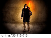 Купить «Ugly wayfarer with burning torch in his hand in front of a crumbly wall concept», фото № 33915013, снято 13 июля 2020 г. (c) easy Fotostock / Фотобанк Лори