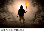 Купить «Man with burning flambeau coming from thicket and looking something», фото № 33918213, снято 13 июля 2020 г. (c) easy Fotostock / Фотобанк Лори