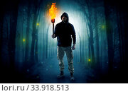 Купить «Mysterious man coming from a path in the forest with burning flambeau concept», фото № 33918513, снято 13 июля 2020 г. (c) easy Fotostock / Фотобанк Лори