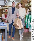 Купить «Smiling couple is satisfied of purchases and walking with package», фото № 33918861, снято 12 марта 2018 г. (c) Яков Филимонов / Фотобанк Лори