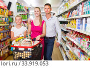 Smiling parents with girl standing with purchases in shop. Стоковое фото, фотограф Яков Филимонов / Фотобанк Лори