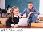 Купить «Emotional university students sitting and reading homework», фото № 33919129, снято 9 марта 2020 г. (c) Яков Филимонов / Фотобанк Лори