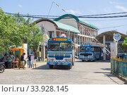 Междугородний автобус на выезде с территории городского автовокзала. Тринкомали, Шри-Ланка (2020 год). Редакционное фото, фотограф Виктор Карасев / Фотобанк Лори