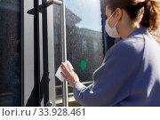 Купить «woman in mask cleaning door handle with wet wipe», фото № 33928461, снято 30 апреля 2020 г. (c) Syda Productions / Фотобанк Лори