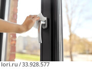 Купить «woman cleaning window handle with wet wipe», фото № 33928577, снято 24 апреля 2020 г. (c) Syda Productions / Фотобанк Лори