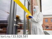 Купить «healthcare worker sealing door with caution tape», фото № 33928581, снято 24 апреля 2020 г. (c) Syda Productions / Фотобанк Лори