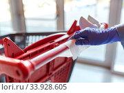 Купить «hand cleaning shopping cart handle with wet wipe», фото № 33928605, снято 30 апреля 2020 г. (c) Syda Productions / Фотобанк Лори
