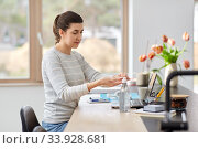 woman spraying hand sanitizer at home office. Стоковое фото, фотограф Syda Productions / Фотобанк Лори