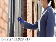 Купить «woman in mask and glove trying to open door», фото № 33928717, снято 30 апреля 2020 г. (c) Syda Productions / Фотобанк Лори