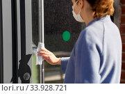 Купить «woman in mask cleaning door handle with wet wipe», фото № 33928721, снято 30 апреля 2020 г. (c) Syda Productions / Фотобанк Лори