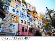 Купить «Hundertwasser house in Vienna, Austria. The Hundertwasserhaus apartment block has colorful facade, undulating floors, a roof covered with earth and grass, and large trees growing from inside», фото № 33929497, снято 27 октября 2019 г. (c) Nataliia Zhekova / Фотобанк Лори