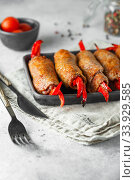 Meat rolls stuffed with sweet red paprika in heat-resistant black dish on a grey background. Стоковое фото, фотограф Nataliia Zhekova / Фотобанк Лори
