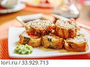Купить «Tempura Maki Sushi (Deep Fried Roll made of Smoked Eel, Crab Meat and Cream Cheese inside) with Spicy Salmon (sake) Gunkan Sushi», фото № 33929713, снято 7 августа 2015 г. (c) Nataliia Zhekova / Фотобанк Лори