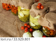 Home canning. Banks pickled tomatoes and baby summer squash. Стоковое фото, фотограф Nataliia Zhekova / Фотобанк Лори