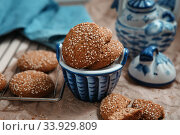 Fresh baked oatmeal cookies with sesame seeds in a cup. Sesame chip cookies on the grid for baking and blue tea set on the table. Стоковое фото, фотограф Nataliia Zhekova / Фотобанк Лори