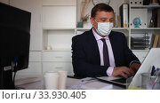 Portrait of adult businessman in surgical medical mask talking at camera. Concept of business people and health care in coronavirus pandemic. Стоковое видео, видеограф Яков Филимонов / Фотобанк Лори