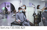 Young woman stylist wearing face mask and gloves working in hairsalon doing haircut and hair styling for male client, new normal due to coronavirus outbreak. Стоковое видео, видеограф Яков Филимонов / Фотобанк Лори