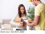 Купить «Young male courier delivering parcel to the office», фото № 33931069, снято 22 ноября 2019 г. (c) Elnur / Фотобанк Лори
