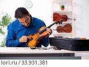 Купить «Young male repairman repairing violin», фото № 33931381, снято 25 октября 2019 г. (c) Elnur / Фотобанк Лори