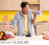 Купить «Young man calculating expences for vegetables in kitchen», фото № 33933285, снято 3 августа 2018 г. (c) Elnur / Фотобанк Лори