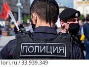 Полицейские в защитных масках обеспечивают безопасность во время публичного мероприятия на улице Тверская в центре города Москвы во время эпидемии коронавируса COVID-19 в России (2020 год). Редакционное фото, фотограф Николай Винокуров / Фотобанк Лори
