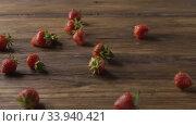 Купить «A woman's hand throws some red ripe wet strawberries, a handful of berries on a wooden table. Tracking slow motion video. Full HD video, 240fps,1080p», видеоролик № 33940421, снято 3 июля 2020 г. (c) Ярослав Данильченко / Фотобанк Лори
