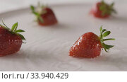 Купить «Close-up ripe red strawberry fruit falls into a plate of water with splashes and drops of water. A few berries lie on the white plate. Slow motion. Soft focus. Full HD video, 240fps,1080p.», видеоролик № 33940429, снято 2 июля 2020 г. (c) Ярослав Данильченко / Фотобанк Лори