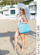 Купить «Sexy girl in swimsuit with umbrella walking from hotel to sea beach», фото № 33941345, снято 10 июля 2018 г. (c) Яков Филимонов / Фотобанк Лори