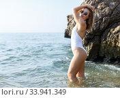Купить «Young female in swimsuit and sunglasses near stones at sea shore», фото № 33941349, снято 10 июля 2018 г. (c) Яков Филимонов / Фотобанк Лори