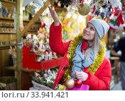 Portrait of young girl choosing xmas gifts on the street market. Стоковое фото, фотограф Яков Филимонов / Фотобанк Лори
