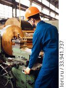 Turner in uniform and helmet works on lathe. Стоковое фото, фотограф Tryapitsyn Sergiy / Фотобанк Лори
