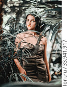 Купить «Gorgeous young 20s woman wearing long evening elegant dress and tiara on head posing surrounded by lush tropical foliage trees. Beauty and fashion concept», фото № 33941917, снято 7 сентября 2014 г. (c) Alexander Tihonovs / Фотобанк Лори