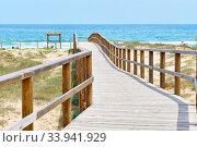 Купить «Wooden empty board walk leading through sandy dunes to Mediterranean Sea and beach of Los Arenales del Sol or Arenals del Sol. Costa Blanca, Europe, Spain. Espana», фото № 33941929, снято 2 июня 2020 г. (c) Alexander Tihonovs / Фотобанк Лори