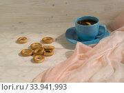 Мелкие баранки и чашка с чаем на деревянном столе около окна. Стоковое фото, фотограф Наталья Гармашева / Фотобанк Лори