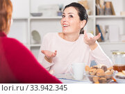 Happy young woman talking with mother at table. Стоковое фото, фотограф Яков Филимонов / Фотобанк Лори