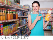 Купить «Female in the supermarket holding juice in bottle», фото № 33942377, снято 6 июня 2017 г. (c) Яков Филимонов / Фотобанк Лори