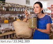 Купить «adult female take a smell natural dried herbs sold by weight in eco shop», фото № 33942389, снято 13 июня 2017 г. (c) Яков Филимонов / Фотобанк Лори