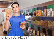female customer choosing natural dried berries sold by weight in eco market. Стоковое фото, фотограф Яков Филимонов / Фотобанк Лори