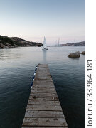Купить «Wooden pier and sailboats sailing in evening calm sea of marvellous Porto Rafael, Costa Smeralda, Sardinia, Italy. Symbol for relaxation, wealth, leisure activity», фото № 33964181, снято 3 сентября 2018 г. (c) Matej Kastelic / Фотобанк Лори