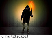 Купить «Ugly scary man with burning flambeau walking in an empty space», фото № 33965533, снято 3 июля 2020 г. (c) easy Fotostock / Фотобанк Лори