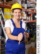 Female in uniform and helmet holding saw and standing near racks in build store. Стоковое фото, фотограф Яков Филимонов / Фотобанк Лори