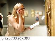 Woman holding brochure in museum of arts. Стоковое фото, фотограф Яков Филимонов / Фотобанк Лори