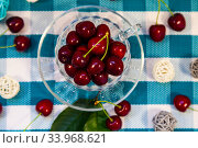 Ripe sweet cherries in a cup on a checkered napkin. Стоковое фото, фотограф Елена Блохина / Фотобанк Лори