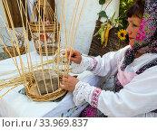Женщина в национальном костюме плетет корзину (2019 год). Редакционное фото, фотограф Вячеслав Палес / Фотобанк Лори